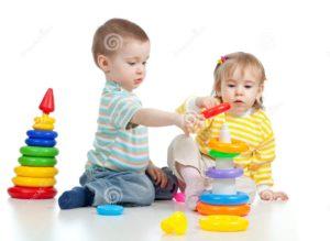 due-piccoli-bambini-che-giocano-con-i-giocattoli-di-colore-23797000